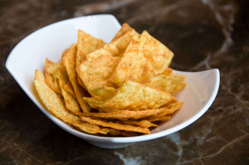 Chips, crisps with seasoning on white plate on the table. Snack close up Chips Crisps Bowl Food Styling Snack Meal Seasoning Food Ready-to-eat Close-up Unhealthy Eating Potato Chip Fried Appetizer Crunchy Deep Fried  Still Life Focus On Foreground Fast Food Nacho Chip