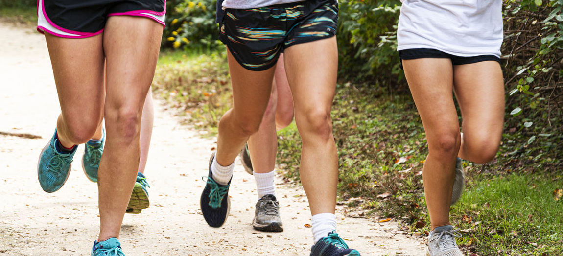 Low section of women running on dirt road