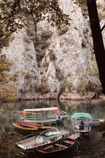 Boats moored on rock by lake