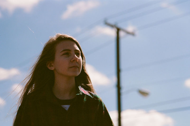Thoughtful young woman looking away against sky