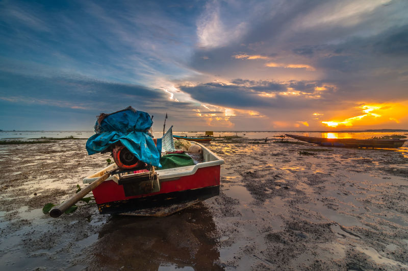 Fishing boat moored at beach against sky during sunset