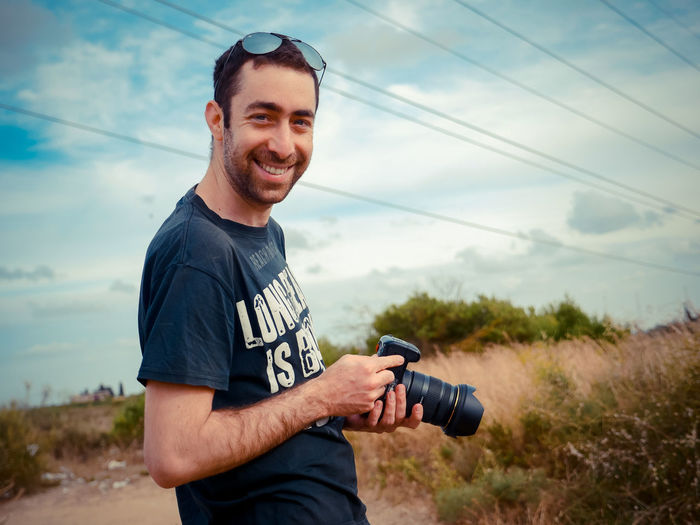 Smiling man holding camera while standing against sky