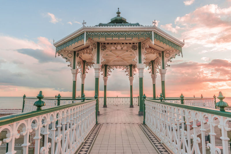 Empty gazebo at brighton pier against sky during sunset