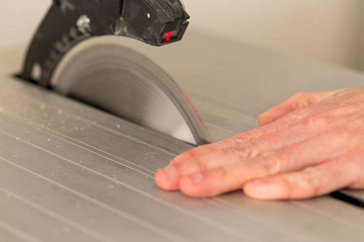 Cropped hand on table saw at workshop