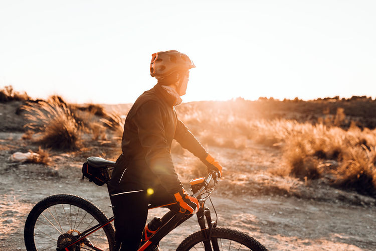 Side view of man riding bicycle on land against sky