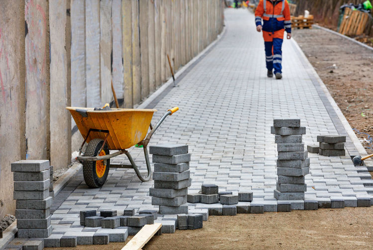 Construction wheelbarrow and stacks of paving slabs against blurred background of lined walkway .
