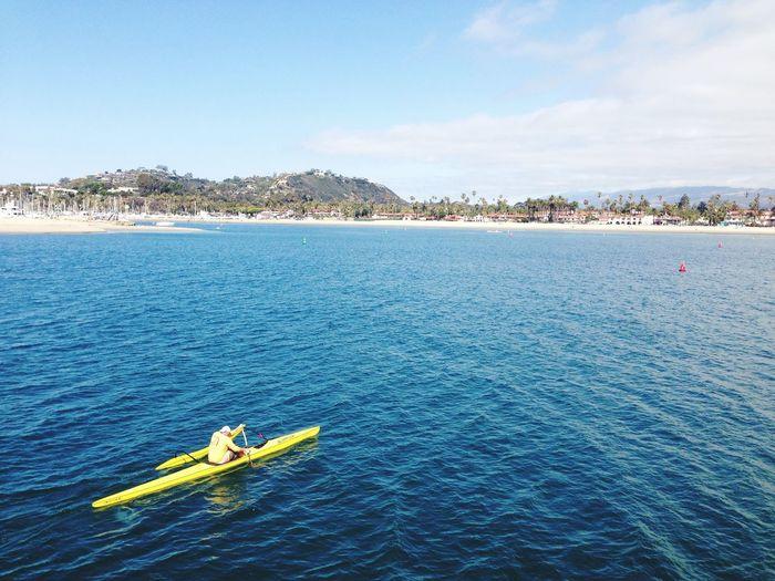 Man Kayaking On Sea Against Sky