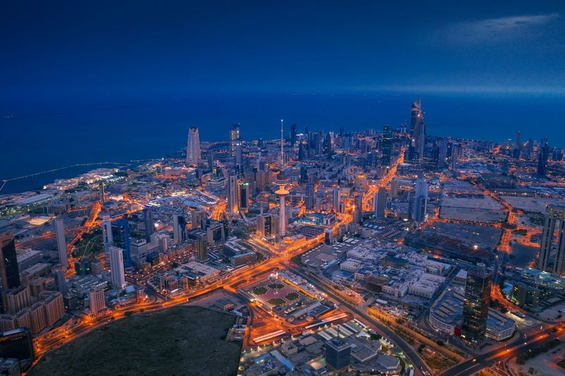 Aerial view of illuminated cityscape by seascape against blue sky at dusk