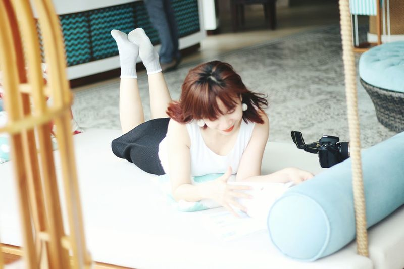 Young Woman Reading Book While Lying On Mat At Home