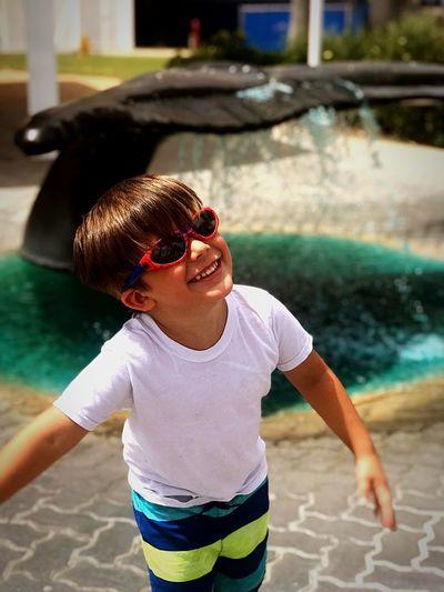 Portrait of happy boy wearing sunglasses on footpath