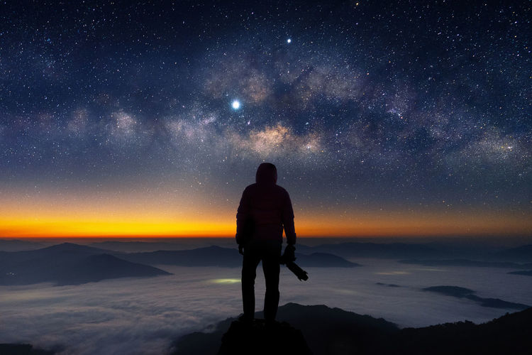 Silhouette of photographer with camera and milky way blackground. Star - Space Sky Scenics - Nature Astronomy Galaxy Beauty In Nature Space One Person Standing Night Real People Star Field Leisure Activity Rear View Tranquility Star Lifestyles Milky Way Silhouette Nature Outdoors Looking At View
