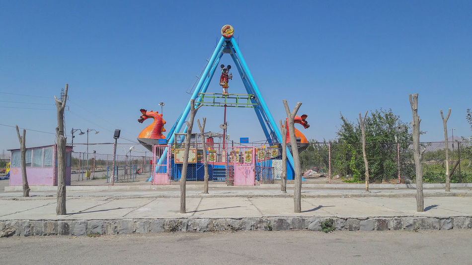 Architecture Blue Childhood Clear Sky Day Enjoyment Fun Jungle Gym Land Leisure Activity Low Angle View Men Nature Outdoor Play Equipment Outdoors People Playground Sand Sky Swing Tree