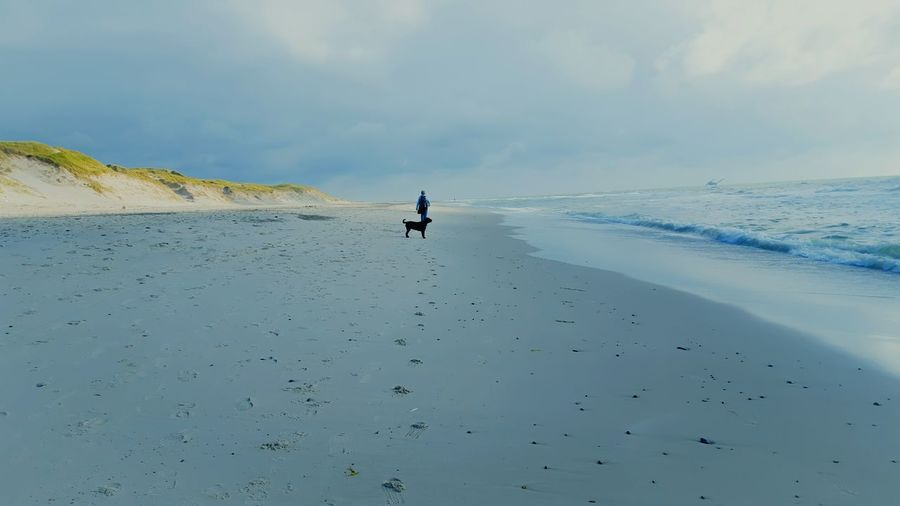 Distant View Of Person And Dog On Shore Against Cloudy Sky