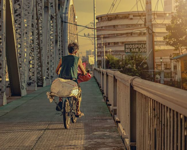 Rear view of man riding bicycle on bridge in city