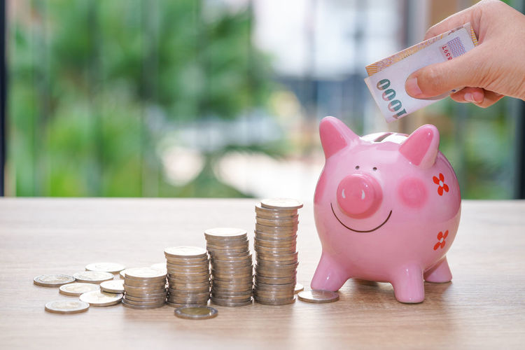 Midsection Of Woman Putting Coin In Piggy Bank At Table