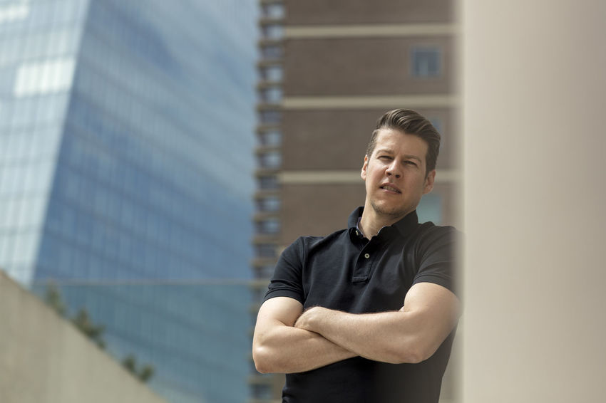 Handsome man leaning his back against a beige wall with his arms crossed. Buildings visible in the background. Adult Looking At Camera Man Skyscrapers Standing Sunny Afteroon Beige Wall Buildings Casual Clothing Caucasian Day Golf Shirt Good Looking Handsome Male Medium Shot Model Outdoors Outside Portrait Posing Summer Urban Waist Up