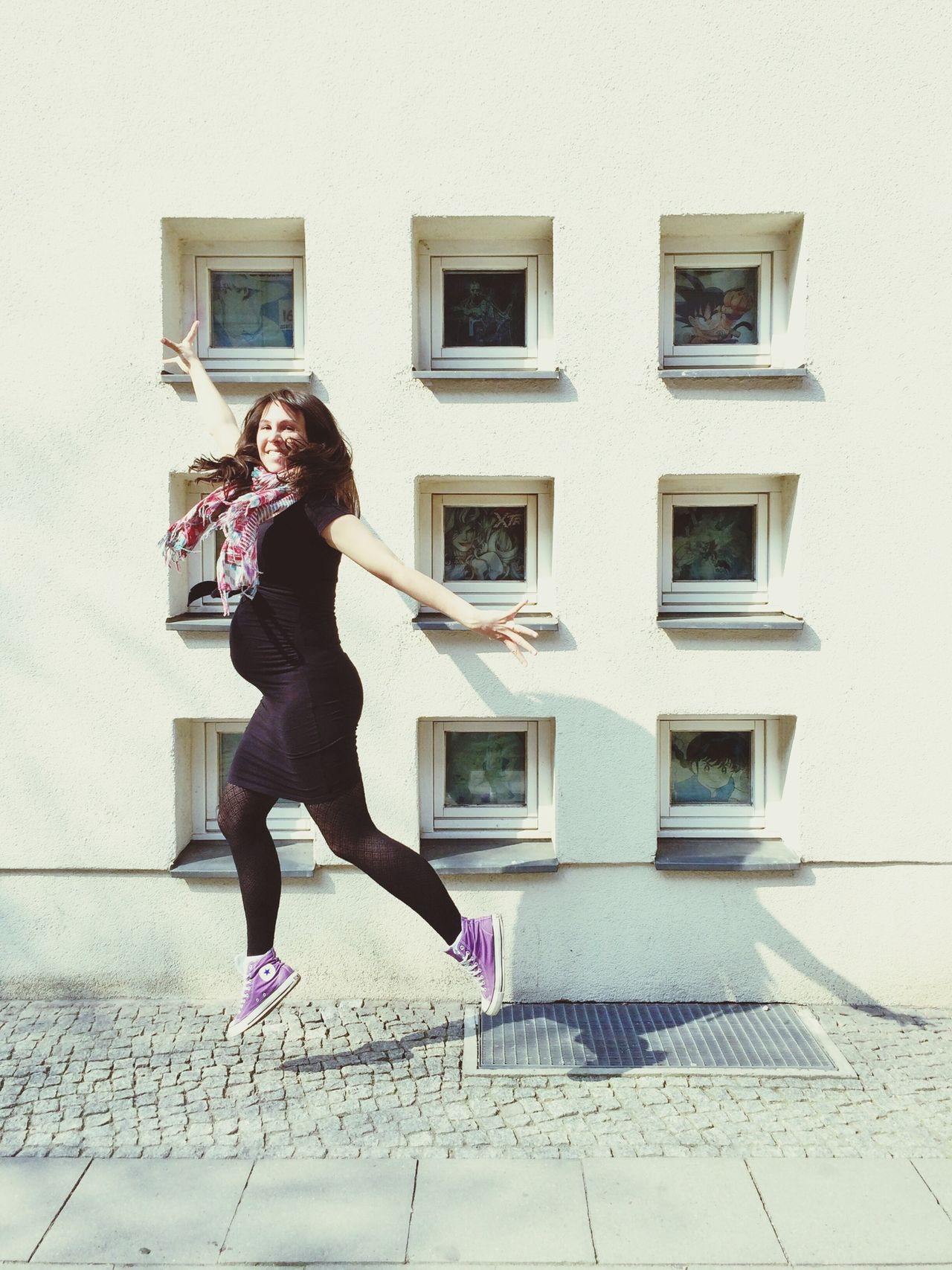 Portrait of pregnant woman jumping on street