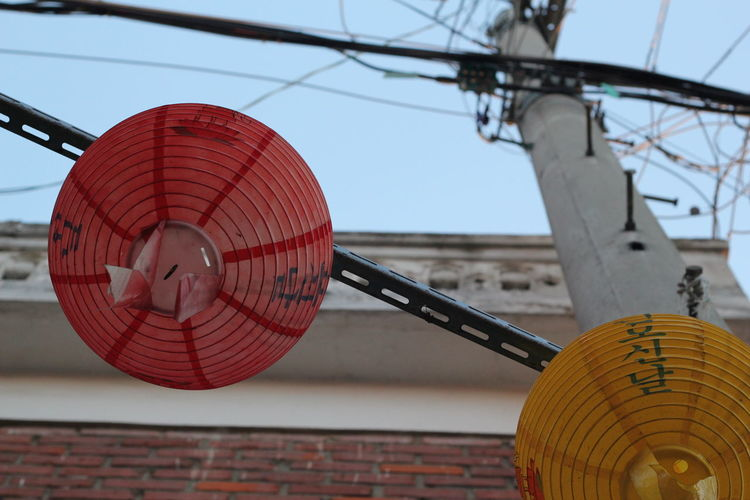 Low angle view of lanterns hanging on pole against building