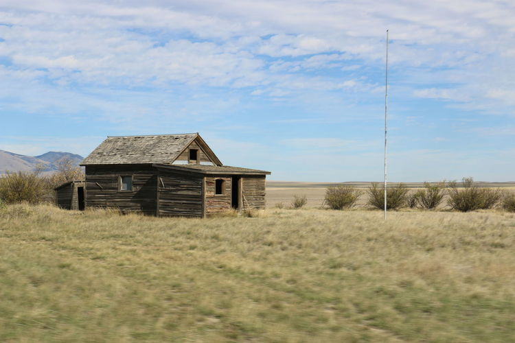 Blue Sky White Clouds Abandoned Architecture Brown Building Exterior Built Structure Cloud - Sky Day Field Flagpole Grass House Nature No People Non-urban Scene Old Rural Schoolhouse Old-fashioned Remote Residential Building Run-down Rural Scene Sky Tranquil Scene Tranquility Weathered
