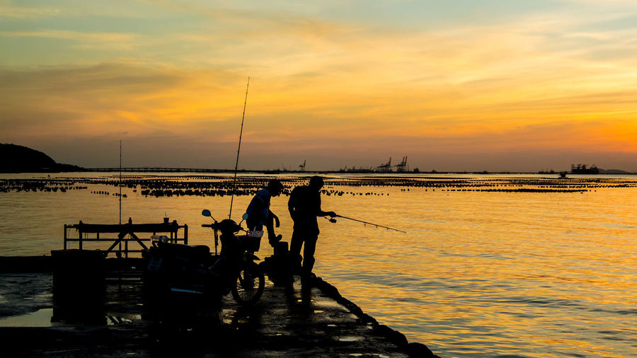 Silhouette men fishing in sea at sunset
