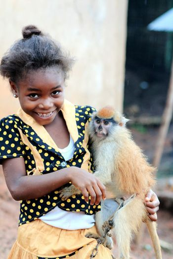 Portrait of happy girl playing with monkey