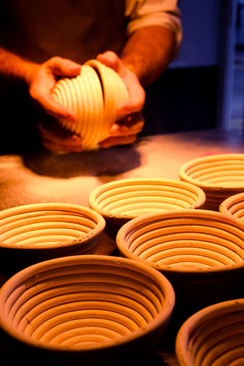 Cropped Hands Of Potter Making Bowls At Pottery Workshop