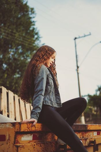 Side view of teenage girl sitting on bench against sky