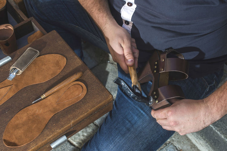 Shoes Shoemaker Craft Leather Hands Handmade Work Tools Real People One Person Men Work Tool Occupation Human Hand Hand Working Midsection Holding Skill  Indoors  Workshop Wood - Material Machinery Human Body Part Hand Tool Equipment Preparation