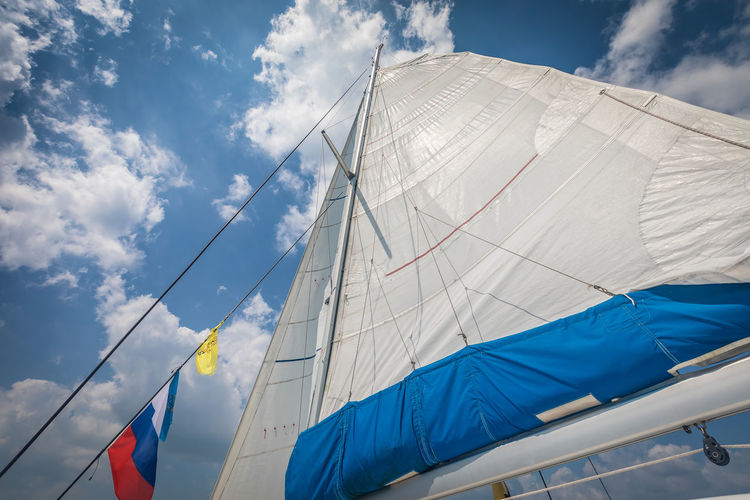 Sky Low Angle View Cloud - Sky Nature Day Blue Sailboat Textile Wind Pole Mast Flag Mode Of Transportation White Color No People Nautical Vessel Environment Outdoors Canvas Patriotism