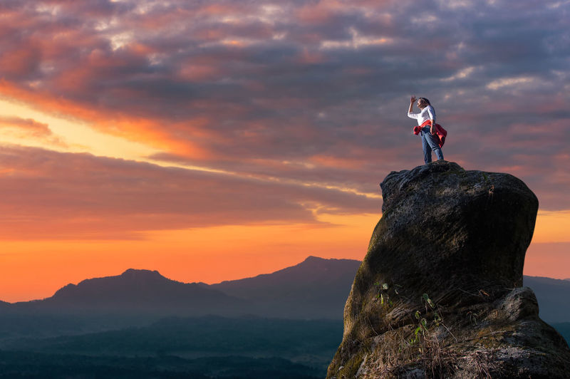 Man standing on rock against mountain during sunset