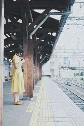 Side view of woman standing on railroad station platform