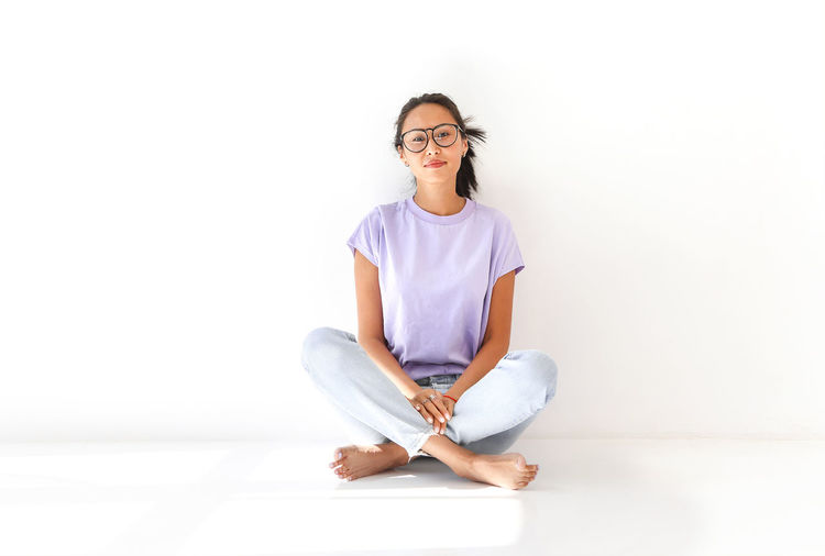 Portrait of a smiling young woman sitting against white background