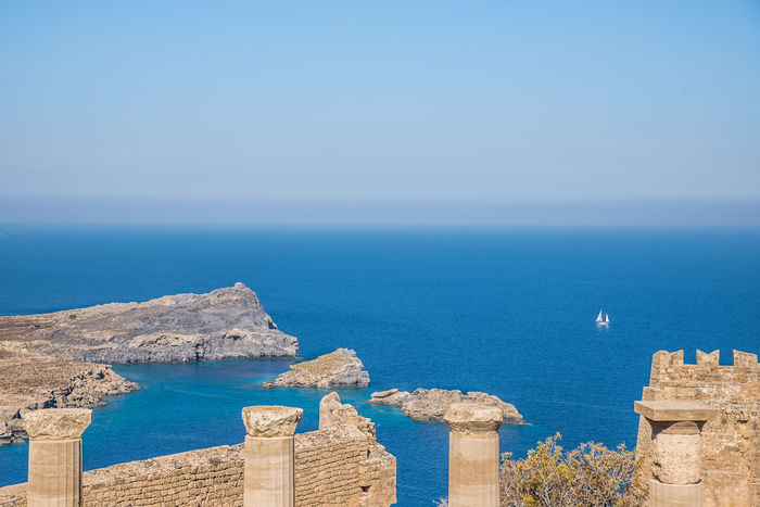 Ancestral View by Anna Wacker Sea Water Sky Scenics - Nature Horizon Horizon Over Water Architecture Blue Nature Beauty In Nature Day No People Clear Sky Built Structure Tranquil Scene Travel Destinations Tranquility Land Sunlight Outdoors Ancient Ruins Acropolis Of Lindos Aegean Ancient Architecture Doric Columns