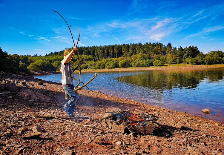 Camp Fire Camping Collecting Sticks Forest Clouds Water Spraying Men Sky Lakeside Shore Tranquil Scene Non-urban Scene Lake