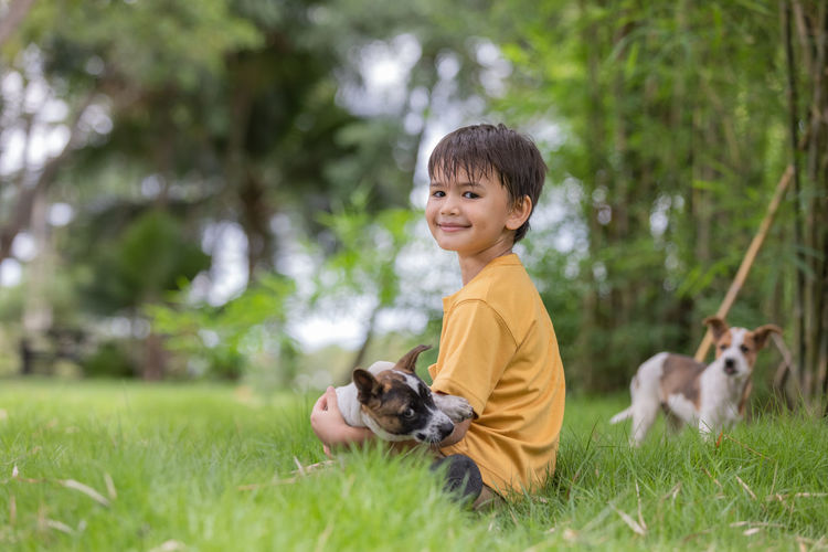 Boy sitting at park with dogs