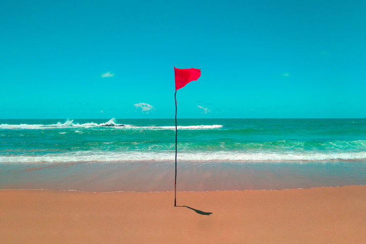 Beach Beauty In Nature Blue Day Flag Horizon Horizon Over Water Land Motion Nature No People Outdoors Red Scenics - Nature Sea Sky Tranquil Scene Tranquility Turquoise Colored Water Wave Wind