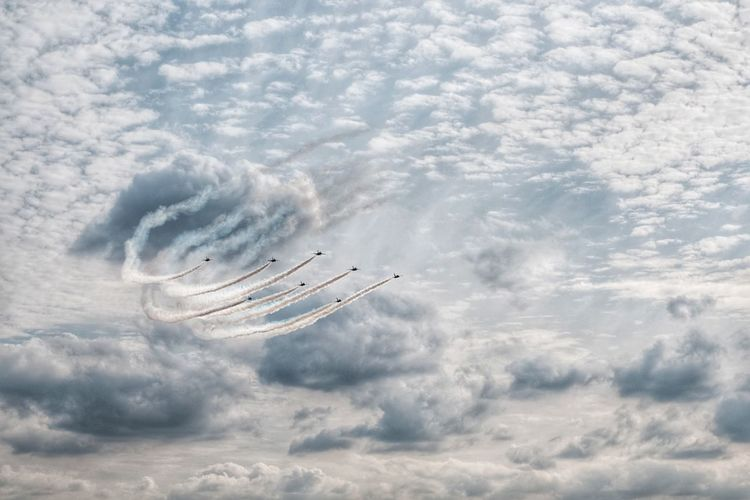 Low angle view of fighter plane in airshow against cloudy sky