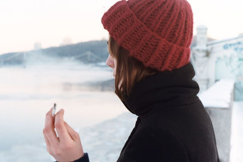 Young woman with cigarette standing at lake against sky