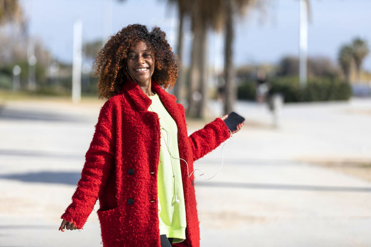 Front view of a young smiling curly afro woman standing outdoors while smiling and listening music by earphones in a sunny day One Person Smiling Happiness Standing Hairstyle Focus On Foreground Young Adult Curly Hair Hair Emotion Red Waist Up Women Lifestyles Day Front View Real People Clothing Leisure Activity Outdoors Warm Clothing Woman African American Afro Denim Happiness Happy Fun Daylight Sunlight
