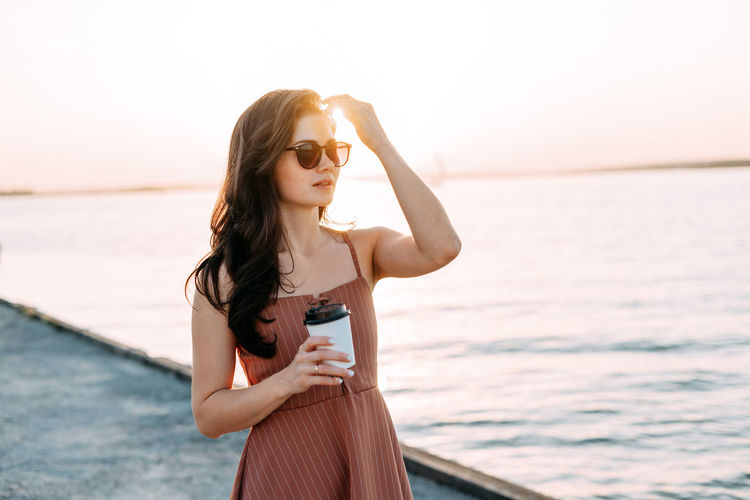 Young woman wearing sunglasses standing against sea