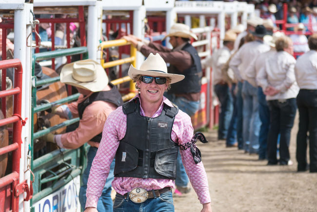 Williams Lake, British Columbia/Canada - July 2, 2016: one of the Wild Horse Race team members smiles for photographers at the 90th Williams Lake Stampede, an internationally famous event. 90th Williams Lake Stampede British Columbia, Canada Canadian Professional Rodeo Association Cowboy Man Rodeo Swagger  Travel Wild Horse Race Candid Confidence  Country Western Cowboy Hat Documentary Editorial  Looking At Camera Male Outdoors People Professional Rodeo Smiling Stampede Team Member Tourism Walking
