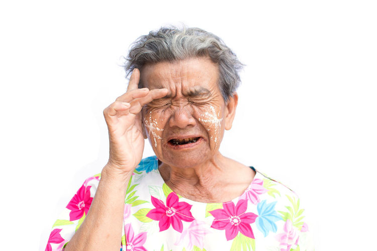 Close-Up Of Tensed Senior Woman With Eyes Closed Against White Background