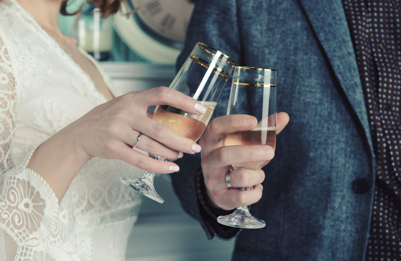 Midsection Of Wedding Couple Toasting Champagne Flutes