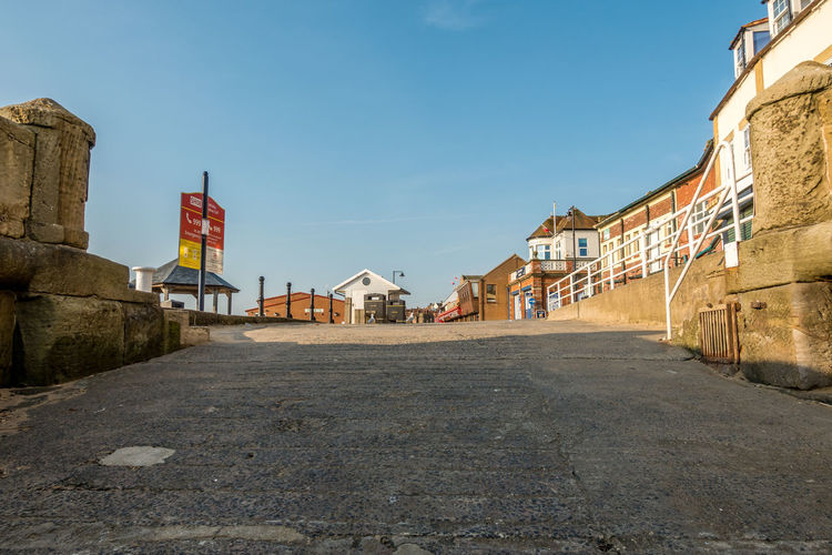 Whitby Whitby Harbour Whitby View Whitby North Yorkshire North Yorkshire Coast North Yorkshire Seaside Town Seaside Slipway Architecture Built Structure Building Exterior Sky Day Clear Sky No People Street House Outdoors Row House Sunlight Blue Building The Way Forward Road
