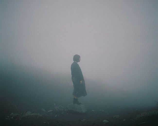 Man standing on landscape in foggy weather