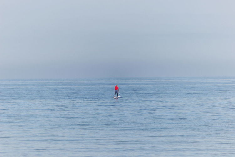 Person on sea against sky