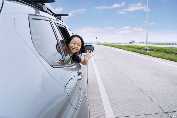Portrait of girl waving from car