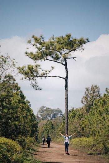 Full Length Of Woman With Arms Outstretched Standing By Tree At Phu Kradueng National Park