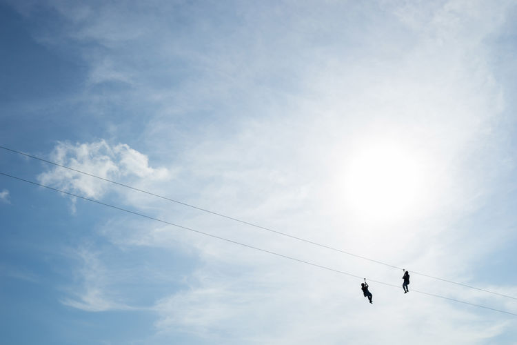 Low Angle View Of People On Zip Line Against Sky
