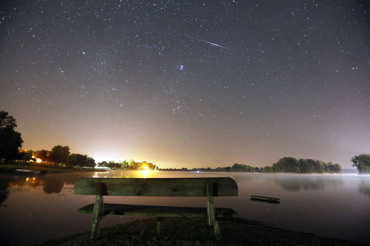 Empty Park Bench By Lake Against Star Field At Night